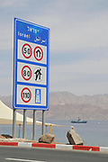 Israeli Speed limits information sign after the Taba border crossing from Egypt into Israel. sraeli navy Dabur class patrol boat in the background