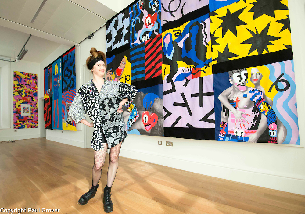 London based,Colchester Born artist/illustrator Hattie Stewart with her work at The House of Illustration at King's Cross for her exhibition On 17 April 2015 Hattie Stewart: Adversary. This is a new body of work from the self-proclaimed professional 'doodle-bomber', in which Stewart takes on glossy advertising imagery with her characteristic homage-meets-satire approach.<br /> Hattie Stewart: Adversary is the first in House of Illustration's series of illustrator commissions – new work from contemporary illustrators to be shown in House of Illustration's South Gallery.Pic Shows Hattie with 'Dont You want me bay' and 'Telecommunications' two of her tapestry's