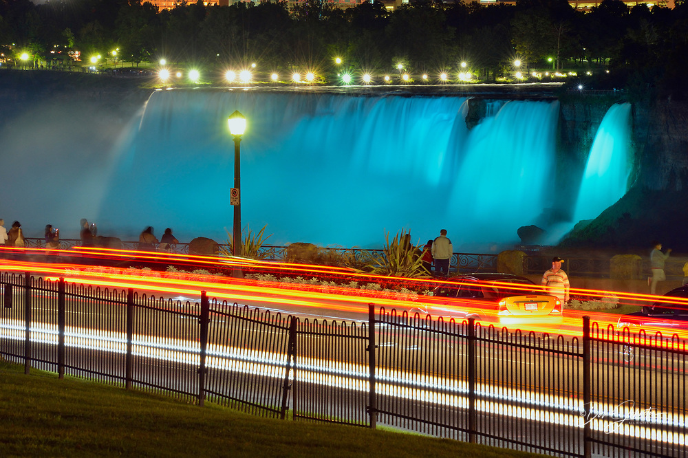 Nighttime at Niagara Falls- Coloured spotlights on the American Falls with traffic on the Niagara Parkway, Niagara Falls, Ontario, Canada