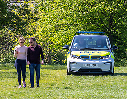 © Licensed to London News Pictures. 19/04/2020. London, UK. A couple go for their daily walk as Police cars patrol Primrose Hill enforcing lockdown rules on social distancing and exercise as Ministers urge councils to keep parks open to the public during lockdown. Photo credit: Alex Lentati/LNP