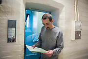 A prisoner stands oustide his cell door reading a letter. HMP/YOI Portland, Dorset. A resettlement prison with a capacity for 530 prisoners. Portland, Dorset, United Kingdom.
