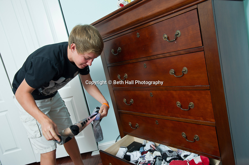 """Winston Robson, 15, of Bentonville, Ark., takes socks made by Rock """"Em Apparel out of his drawer on Tuesday, Sept. 10, 2013, in Bentonville, Ark. Robson owns several pair of the custom Nike Elite socks. Photo by Beth Hall"""