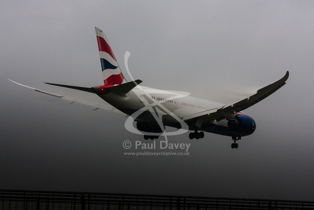 """January 3rd 2015, Heathrow Airport, London. Low cloud and rain provide ideal conditions to observe wake vortexes and """"fluffing"""" as moisture condenses over the wings of landing aircraft. With the runway visible only at the last minute, several planes had to perform a """"go-round"""", abandoning their first attempts to land. PICTURED: A British Airways Boeing 787 Dreamliner prepares to land on Heathrow's runway 27L"""