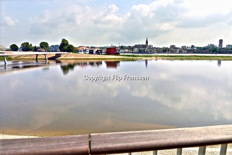 Nederland, Nijmegen, 3-6-2016De bijna 4 km. lange nevengeul van de Waal bij Lent. Grootste onderdeel van de vele werken van Rijkswaterstaat om bij hoogwater een betere waterafvoer in de rivier te hebben. Het dorp veurlent komt op een kunstmatig eiland te liggen met twee kleinere bruggen als ontsluiting. Een voetgangersbrug, de steltlopersbrug voor wandelaars naar het recreatiegebied en een andere, de Promenadebrug, voor normaal verkeer met eronder een voetpad . Ruimte voor de rivier, water, waal. In de nieuwe dijk wordt een drempel gebouwd die stapsgewijs water doorlaat en bij hoogwater overloopt. The Netherlands, Nijmegen Measures taken by Nijmegen to give the river Waal, Rhine, more space to flow during highwater and to prevent the risk of flooding. Room for the river. Reducing the level, waterlevel. Large project to create a new paralel gully, an extra flow of water, so the river can drain more water during highwater. Due to climate change and expected rise, increase of the sealevel, the Dutch continue to protect their land from the water. Foto: Flip Franssen