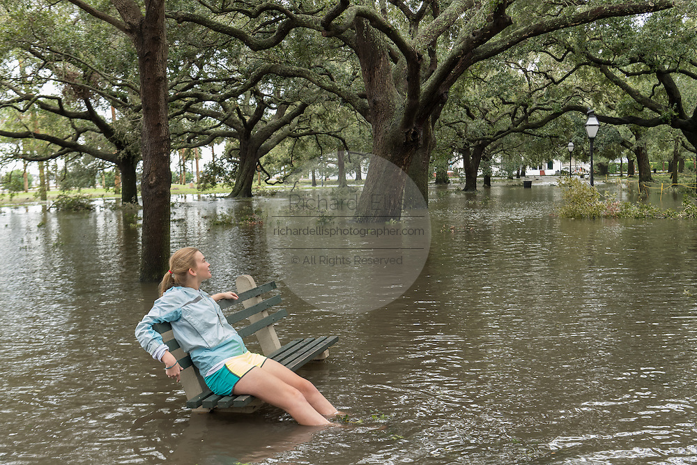 A young girl sits on a park bench surrounded by flood water in White Point Gardens in historic downtown after Hurricane Matthew passed through causing flooding and light damage to the area October 8, 2016 in Charleston, South Carolina. The hurricane made landfall near Charleston as a Category 2 storm but quickly diminished as it moved north.