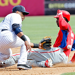 March 4, 2012; Tampa Bay, FL, USA; Philadelphia Phillies right fielder Domonic Brown (9) slides into second past New York Yankees second baseman Robinson Cano (24) during spring training game at George M. Steinbrenner Field. Mandatory Credit: Derick E. Hingle-US PRESSWIRE