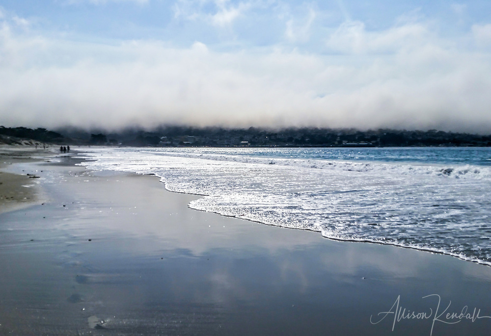 A blanket of heavy fog rests on the landscape of Monterey, with the waves and sand of Del Monte beach in the foreground. California, 2016