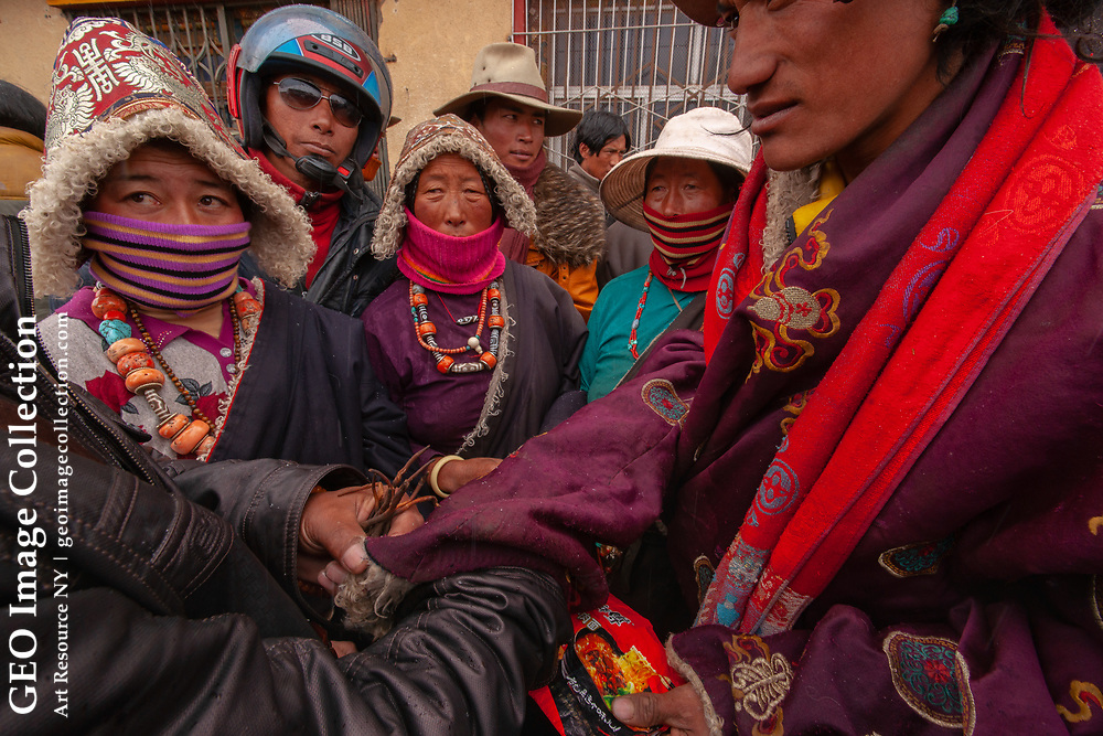 Bargaining Ttibetan style, buyer and seller haggle with hand signals inside coat sleeves shielded from the curios eyes of the crowd at the local market selling Yartsa gompo, Mostly Tibetan nomad traders. Sichuan, China