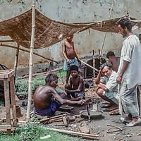 A blacksmith waits by his bed of coals his outdoor stall near Dhaka, Bangladesh.