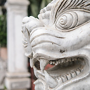 A white marble statue of a lion stands guard outside a temple in Hanoi, Vietnam. See from side profile.
