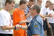Policeman congratulating ribbon winner. Special Olympics U of M Bierman Athletic Complex. Minneapolis Minnesota USA
