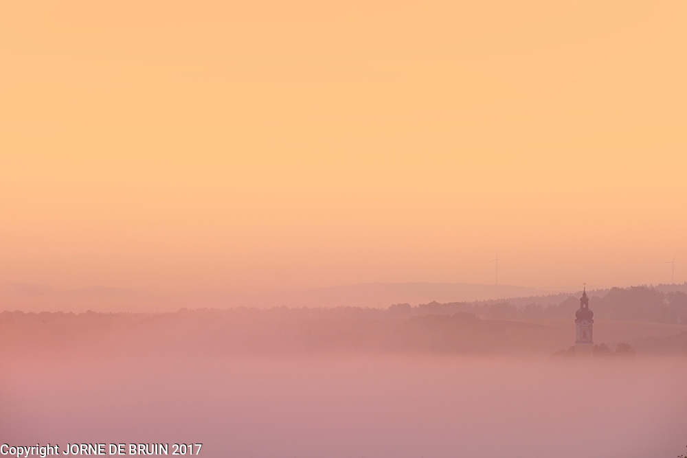 A lone church tower sticks above the mist covering the bavariahn landscape in the early morning sunrise.