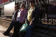 Three family members watch unseen event on opposite side of Piccadilly in central London.