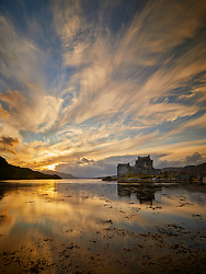 Brightly lit sunset clouds stream across the sky above Eilean Donan Castle in Scotland and reflected in the water of Loch Duich.<br /> Scotland, UK