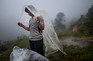 A Hmong porter covers himself with rain coat during a rainy hike up Mt. Fansipan on Cat Cat route, Lao Cai Province, Vietnam, Southeast Asia