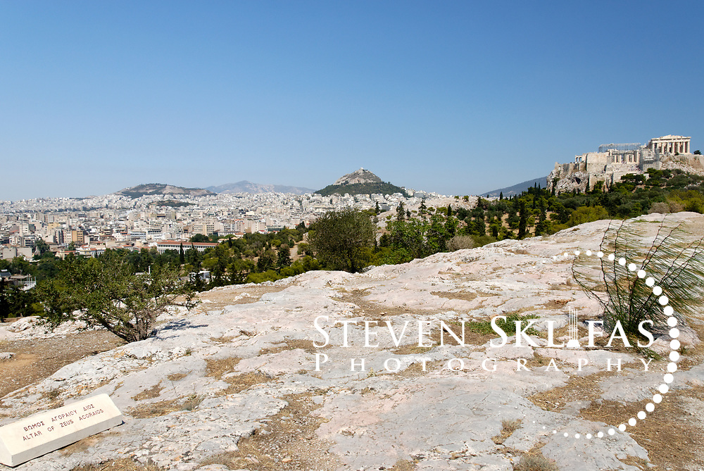 Pnyx Hill. Athens. Greece. View on Pynx Hill of the original location of the 4th century BC Altar of Zeus Agoraios which was moved to the Agora during the Augustan period (1st century).  In the background is the Acropolis and Lykavittos Hil.  Pynx Hill was where speakers including great statesmen's addressed the citizens Assembly during the 5th and 4th centuries BC.  The Assembly met 40 times a year to discuss and vote on proposed legislation and at least 5000 citizens were required to attend each gathering.