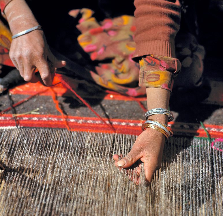 A weaver works on a woolen rug in the Shibar Pass area of Afghanistan.