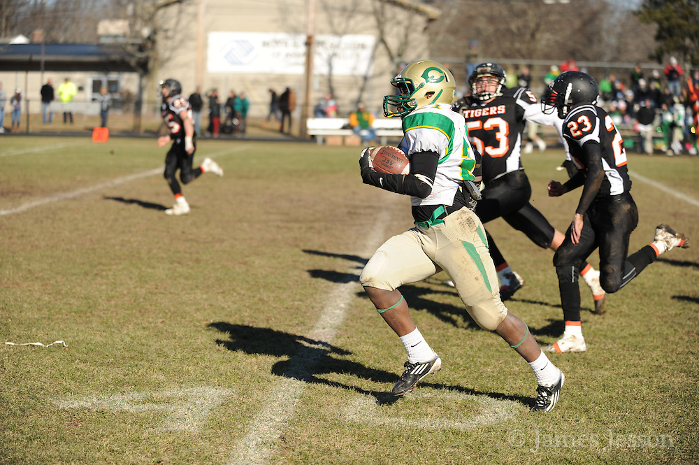 Clinton High School senior Ben Lazare carries the ball down the field under pressure during the Thanksgiving Day game against Maynard High School at Alumni Field in Maynard on Thursday morning. Wicked Local Photo/James Jesson