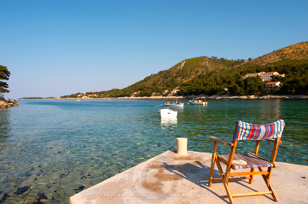 View over the Brna bay, sun deck chair in the foreground on a jetty pier, boats moored in the bay on the water. Prizba village. Korcula Island. Prizba, Riva Apartments, Danny Franulovic. Korcula Island. Dalmatian Coast, Croatia, Europe.