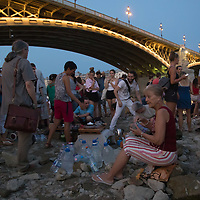 Some hold a tea ceremony in a large group of people stand on a reef under a bridge emerging from the water because of the low water level of River Danube in central Budapest, Hungary on Aug. 22, 2018. ATTILA VOLGYI