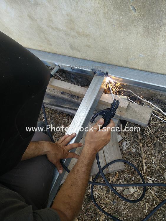 Metal worker welds a metal frame