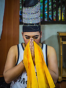 25 SEPTEMBER 2016 - BANGKOK, THAILAND: A Likay performer prays while getting into character before a Likay performance in Pom Mahakan Fort. The performance was to support residents of the old fort  who are fighting eviction orders by the city of Bangkok. City officials have made repeated attempts to evict people since Sept 3, 2016, but about 44 families are still living in the community. Likay is a form of popular folk theatre from Thailand. It uses a combination of extravagant costumes, barely equipped stages and vague storylines. The performances depend mainly on the actors' skills of improvisation and the audiences' imagination. There used to be several Likay troupes based in the old fort, but they left the community more than 50 years ago. The troupe that performed Sunday night was an amateur troupe comprised of college students and office workers.      PHOTO BY JACK KURTZ