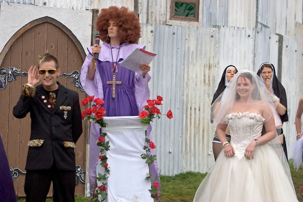 A couple get married outside the Chapel of love and loathing in the Lost Vagueness area at the Glastonbury festival.