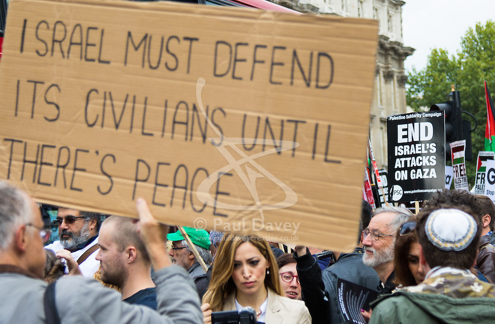 Whitehall, London, September 9th 2015. Two banners sum up the root of two nations' intractible issue as pro Palestinian and Israeli counter-protesters clash in Whitehall as the Palestinian Solidarity campaign demands the arrest of Israel's PM Benyamin Netanyahu for war crimes in the 2014 war with Palestinians in Gaza.  // Contact: paul@pauldaveycreative.co.uk Mobile 07966 016 296