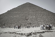 Black and white photo of the Khufu (Cheops in Greek) pyramid showing the entrance and scale of the massive structure