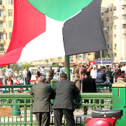 Two men take in the scene as a Palestinian flag flies in Cairo's Tahrir Square.