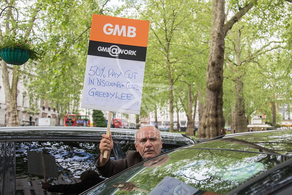 """Mayfair, London, May 24th 2016. Drivers from minicab operator Addison Lee bring traffic to a standstill in Berkely Square, outside of the offices of owner Carlyle Group, in protest against new """"unfair"""" pay rates as the company battles to compete with cut-price Uber, with some drivers claiming they are earning as little as £4.99 per hour. PICTURED: GMB protesters join minicabs as they sound their horns outside Landsdowne House, where Carlyle Group is headquartered"""