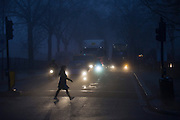 Pedestrian crosses commuter traffic at dawn on a foggy morning in south London.