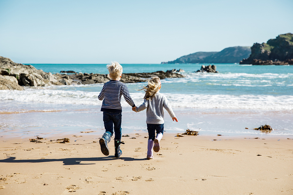 Boy and girl holding hands and runing towards the sea on the beach at Greve de L'Ecq on a sunny Spring day in Jersey