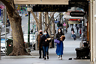 A view of a near empty Collins Street with three women wearing masks walking past a homeless man during COVID-19. After seeing another 177 cases overnight and further outbreaks in nursing homes, Metropolitan Melbourne and the Mitchell Shire are in lockdown following the rise of active cases to 1,612. The new restrictions came into effect on Thursday 9 July with residents in lockdown areas under stay at home orders for the next six weeks. (Photo be Dave Hewison/ Speed Media)