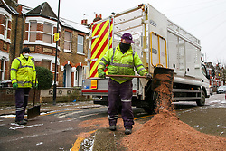 © Licensed to London News Pictures. 09/02/2021. London, UK. Haringey Council workers spread grit over the pavement as snow and freezings temperatures continue in the capital. Photo credit: Dinendra Haria/LNP