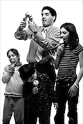 """(DENVER, Co. - Shot 1/27/2005).Assistant Majority Leader Rep. Michael Garcia, D - Aurora dishes up some healthy scoops of ice cream for his nephew Christopher Beall (center), 5, and his nieces Sophia Beall (left), 6, and Alexandra Garcia (right), 12. He may come off as a serious representative while working on the Finance Committee and protecting Colorado's finances but around his family he is the self-proclaimed """"fun time uncle"""". He has been a representative since 2000..(Photo by MARC PISCOTTY / ©2005)"""