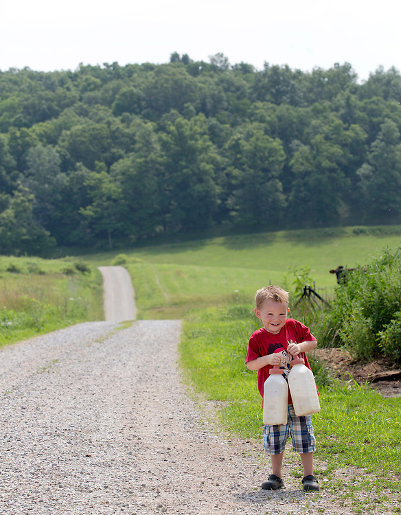 Harlan carries milk out to feed the new calves at Laurel Valley Creamery near Galipolis. (Will Shilling/CRAVE)