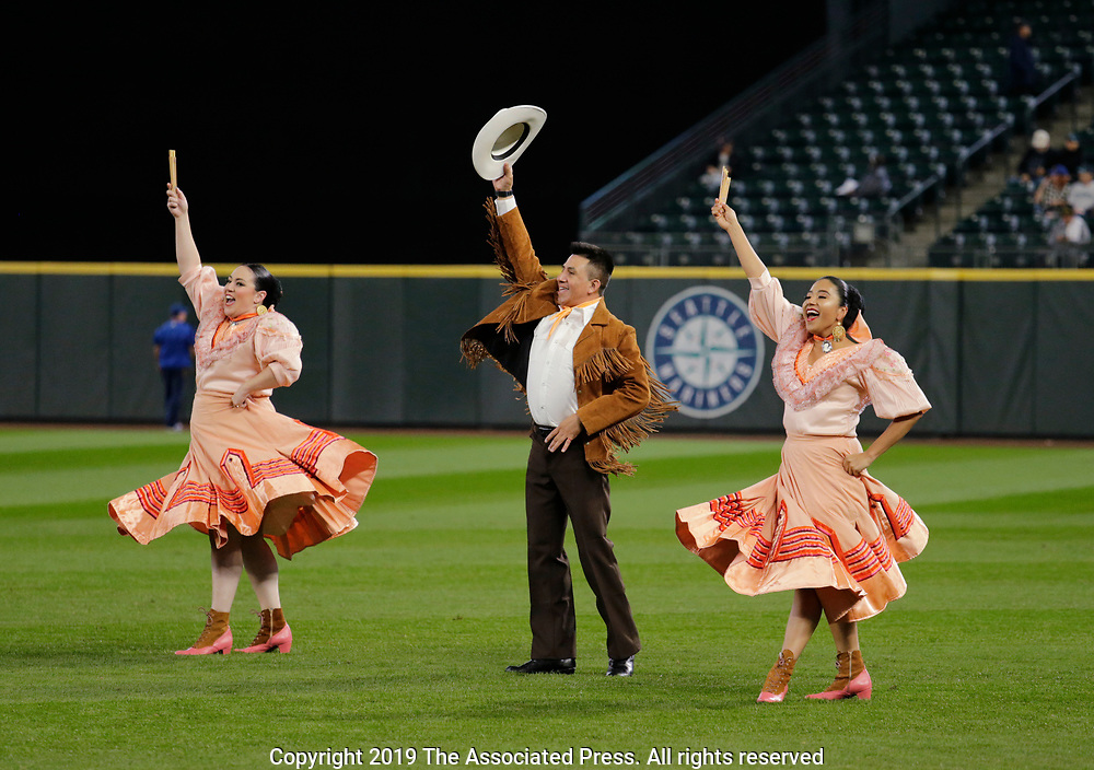 Bailadores de Bronce dancers perform on the field for a salute to Latin American Biesbol Day before a baseball game between the Seattle Mariners and the Chicago White Sox, Sunday, Sept. 15, 2019, in Seattle. (AP Photo/John Froschauer)