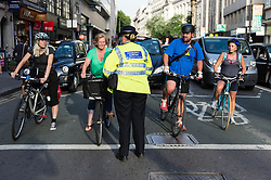© Licensed to London News Pictures. 21/08/2013. London, UK. A community support officer conducts safety checks on road users at Holborn traffic lights yards from the spot where cyclist Alan Neve was killed by a tipper truck on the 15th July. The checks are to highlight the need to leave room for cyclists at traffic lights - the cyclist in the green top  had overshot the area reserved for cyclists before moving back behind the line.  Photo credit : Richard Isaac/LNP