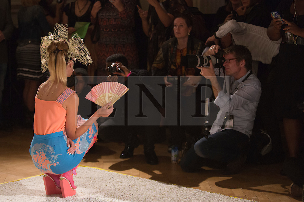 © Licensed to London News Pictures. 13/09/2013. London, England. A model is having her picture taken at the presentation of Spring/Summer 2014 collection by designer Ekaterina Kukhareva at Fashion Scout, Freemason's Hall, during London Fashion Week. Millinery Designer: Lara Jensen. Photo credit: Bettina Strenske/LNP