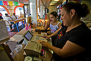 """Lourdes Alvarez, restaurant owner and chef takes a phone order in her family's Mexican restaurant, Los Dos Laredos, in Chicago, Illinois while her daughter, Alejandra, checks her mobile phone after school. (From the book What I Eat: Around the World in 80 Diets.) The caloric value of her typical day's worth of food on a day in the month of September was 3,200 kcals. She is is 39; 5'2.5"""" and 190 pounds. She grew up in an apartment above Los Dos Laredos, where she still helps out two days a week. Other days she spends long hours at her own restaurant in Alsip, Illinois. MODEL RELEASED."""