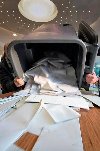 Nederland, Ubbergen, 23-5-2019 Kiezers, burgers, stemgerechtigden, brengen hun stem uit voor het europees parlement bij het stembureau in een middelbare school . De stembus wordt leeg gemaakt. Stembiljetten liggen op een tafel.Foto: Flip Franssen