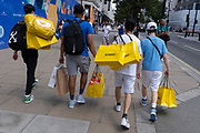 Young Men carry their yellow Selfridges shopping bags purchases on Oxford Street in the West End on Covid 'Freedom Day'. This date is what Prime Minister Boris Johnson's UK government has set as the end of strict Covid pandemic social distancing conditions with the end of mandatory face coverings in shops and public transport, on 19th July 2021, in London, England.
