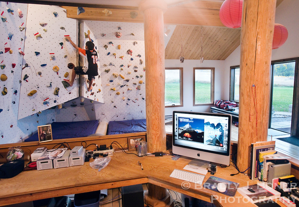 Jimmy Chin's nephew, Sasha Profatilova, climbs on the bouldering wall in the office/bedroom of Chin's Victor, Idaho, home. Chin, a professional photographer and climber, built the wall so he could train while he was in-between expeditions.