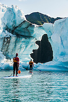 Two adults on stand up paddle boards (SUP) observe hole melted in iceberg on Bear Lake in Kenai Fjords National Park, Alaska.