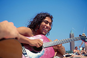 Man laughing while playing a guitar at Jones Beach, New York.