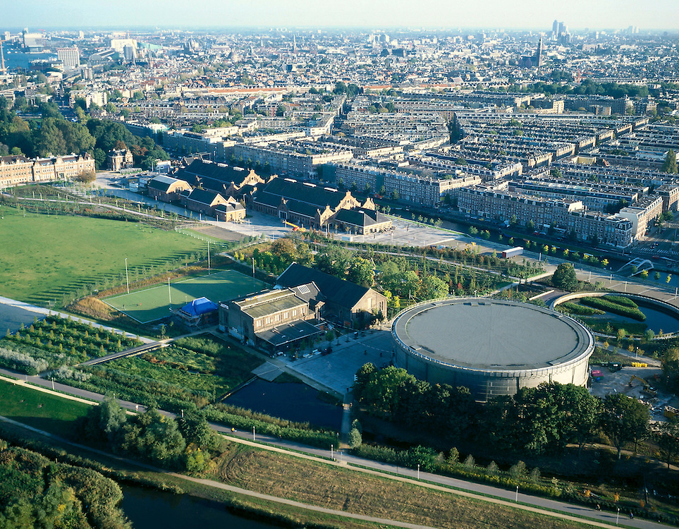 Nederland, Amsterdam, Westerpark,  17-10-2005; luchtfoto (25% toeslag); de gerenoveerde gebouwen op het terrein van de voormalige Westergasfabriek; het ernstige vervuilde terrein is inmiddels gesaneerd en vormt het nieuwe Westerpark; de gerenoveerde fabrieksgebouwen hebben een culturele bestemming gekregen; direct grenzend aan het terrein de Haarlemmerweg met daarachter de Staatsliedenbuurt; uiterst links voormalig directiegebouw, nu Stadsdeelkantoor (Stadsdeel Westerpark); onder rechts de Gashouder (landmark); manifestaties, tentoonstelling, expositie, cultuur, industrieel en cultureel erfgoed; milieu, bodemverontreiniging, gif ..zie ook andere (lucht)foto's van deze lokatie..foto Siebe Swart