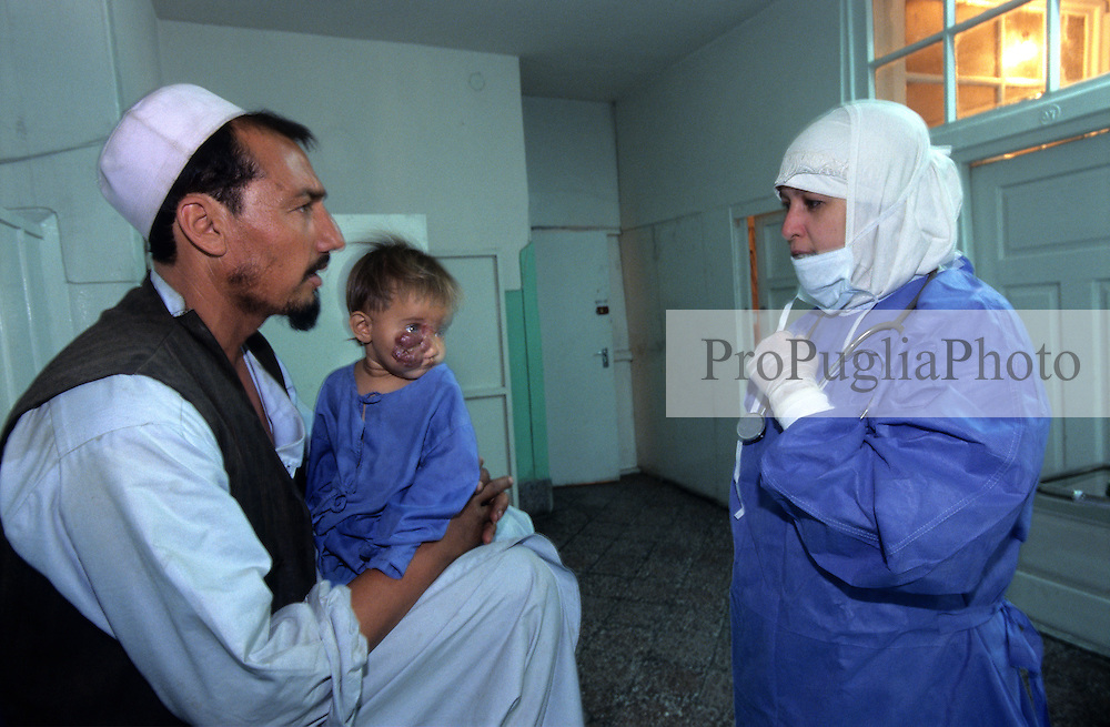 KABUL 16 August 2005..Maiwand Hospital, Plastic Surgery....A nurse is talking to Janat before his daughter is taken into the Operation Room.....Shabana. a nine months old Afghan girl, has been diagnosed with a 'neurofibroma'. This is a tumor or growth located along a nerve or nervous tissue. It is an inherited disorder. If left unchecked, a neurofibroma can cause severe nerve damage leading to loss of function to the area stimulated by that nerve.....The Rehabilitative Surgery Unit (RSU) at Maiwand Hospital is fully supported by the French NGO Medical Refresher Courses for Afghans (MRCA), also by the French Minister of Foreign Affairs, and by the Embassy of Japan under the Grant Assistance for Grassroots Project (GAGP). The Italian NGO Operation Smile Italia Onlus provides training to the Doctors. ....Maiwand Hospital dates back to the rein of Nadir Shah in the 1930s.