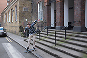 Skateboarder jumps down a small flight of steps at a prime skateboarding spot in Southwark, London, UK.