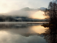 Early morning mist rises on Alta Lake, autumn in Whistler, BC Canada